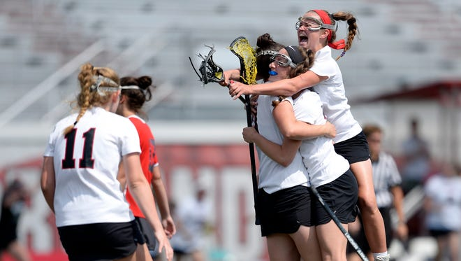 Penfield's Lucy Rugaber, right, and Elisa Faklaris hug Morgan Cox after her game-winning goal during a Class A semifinal at the NYSPHSAA Girls Lacrosse Championships in Cortland, N.Y., Friday, June 8, 2018. Penfield advanced to the Class A championship game with a 9-8 overtime win over North Rockland-I.