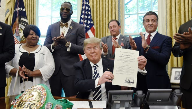 "President Donald Trump holds a signed Executive Grant of Clemency  for  boxer ""Jack Johnson "" in the Oval Office of the White House in Washington May 24, 2018. Attending the event from L to R : Linda Haywood, Great great niece of Jack Johnson, Deontay Wilder, Keith Frankel, Sylvester Stallone, and Lennox Lewis."