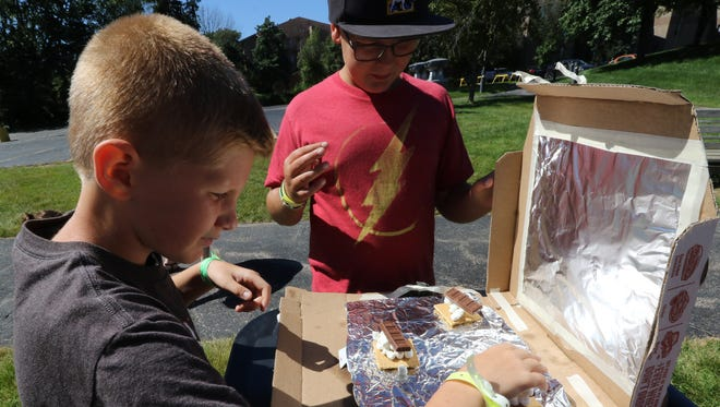Jacob Gebert (left) and Eli Hartley add chocolate to the graham crackers and marshmallows in their solar s'more oven on July 6 during a weeklong Cardboard Creations camp at Wauwatosa's Suburban YMCA.