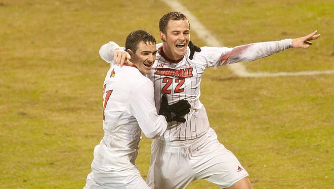 Louisville Cardinals' midfielder Ben Strong, left, hugs teammate Louisville Cardinals' midfielder-defender Tim Kubel after Kubel scores the winning goal against the St. Louis Billikens, beating them 2-1 to advance in the NCAA soccer playoffs.23 November 2014