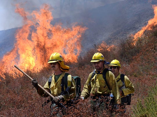 Firefighters battle the Blue Cut Fire along Swarthout Canyon Road in the Cajon Pass, north of San Bernardino, California, on Aug. 16, 2016.