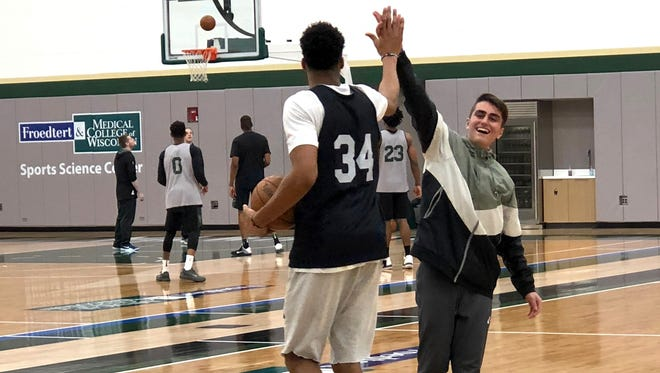 Gianni Antetokounmpo high-fives with Dimitris Zamanis, a 15-year-old Greek boy who spent time with the Milwaukee Bucks superstar Tuesday thanks to Make-A-Wish and the Bucks.