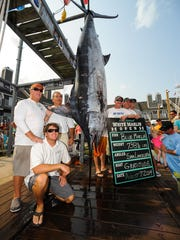 Sam Lacelotta holds the sign as the angler who caught the winning blue marlin in the 2014 White Marlin Open.
