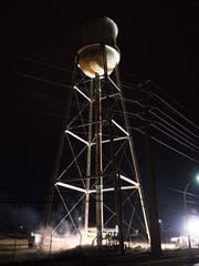Demolition crews prepare the old water tower for demolition at the site of the old Playtex plant in Dover.