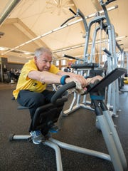 Gary Whalen of Middletown stretches his back during his LIVESTRONG at the YMCA workout.