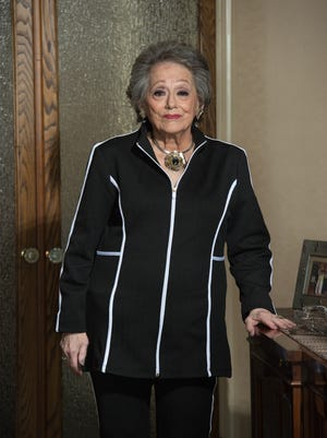 Ruth Pernick wears a black textured pants suit with white piping accents from Chico's with JG black and white snakeskin strapped black flats.