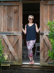 Judy Diogo Schrock wears a flowing sleeveless navy shirt from Talbots; vibrant print ankle-length pants from Ann Taylor; and strappy navy blue sandals from Talbots.