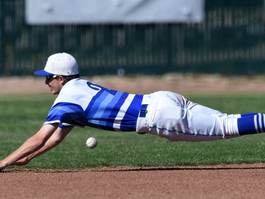 McQueen's Logan Anderson dives to catch a Reno hit during Thursday 's game at McQueen.