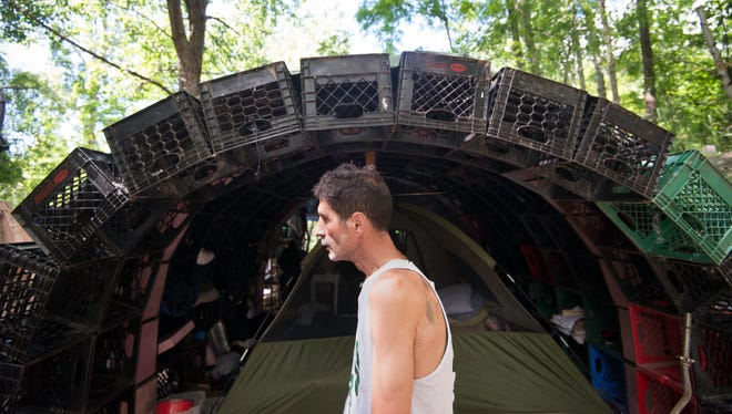 A homeless man in Burlington stands at his milk crate shelter in 2012.
