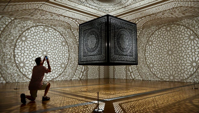 "A man photographs Anila Quayyum Agha's installation ""Intersections"" on the first day of the ArtPrize competition display at the Grand Rapids Art Museum."