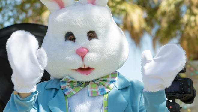 The Easter Bunny, who was available for pictures, waves at the camera on Saturday, March 31, 2018, during SpringFest at Young Park.