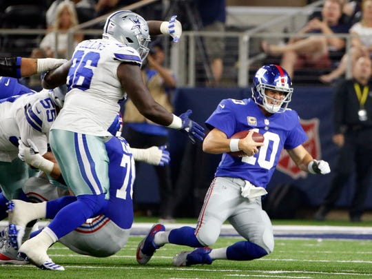 Dallas Cowboys defensive tackle Stephen Paea (55) and defensive tackle Maliek Collins (96) chase New York Giants quarterback Eli Manning (10) for a sack in the second half of an NFL football game, Sunday, Sept. 10, 2017, in Arlington, Texas.