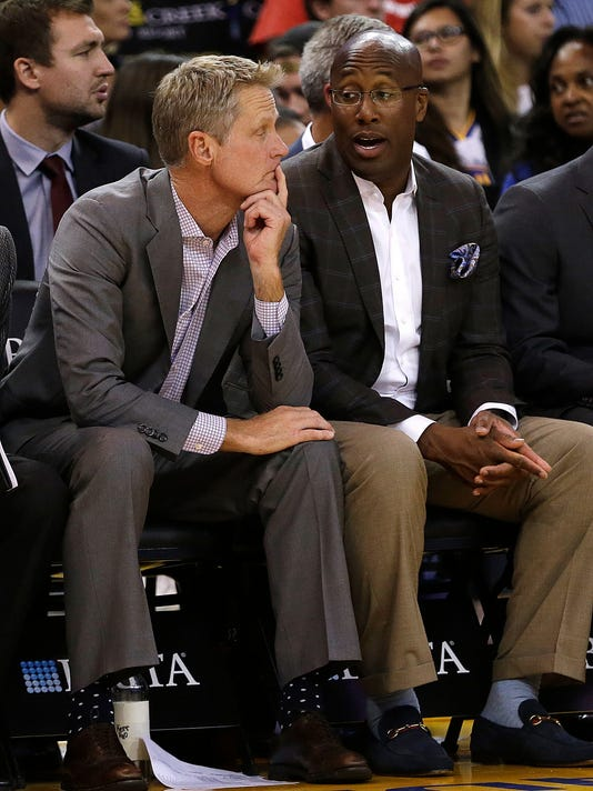 Golden State Warriors coach Steve Kerr, left, sits beside assistant coach Mike Brown during the first half of a preseason NBA basketball game against the Denver Nuggets Saturday, Sept. 30, 2017, in Oakland, Calif. (AP Photo/Ben Margot)