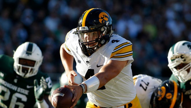 Iowa quarterback Nate Stanley, center, looks to hand off against Michigan State's Brandon Randle, left, and Raequan Williams, right, during the second quarter of an NCAA college football game, Saturday, Sept. 30, 2017, in East Lansing, Mich. (AP Photo/Al Goldis)