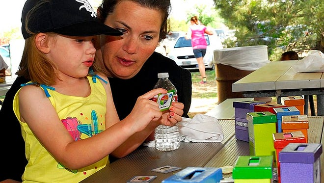 Kenzey and Kerri Ricks play Food Group Bingo at the annual Healthy Kids Day in Kiwanis Park in this file photograph. Health Kids Day returns April 22 to the park.