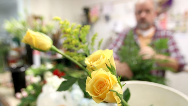 Ruth Messmer Florist floral designer Darryl Cummings works on an arrangement Tuesday before the big Valentine's Day rush this week.