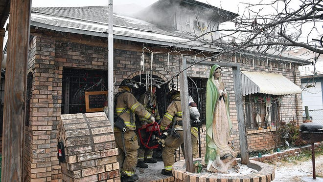 Wichita Falls firefighters carry equipment into a home on Martin Luther King Jr. Boulevard near Third Street Wednesday morning