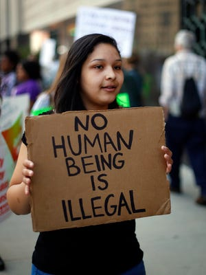 In this May 16, 2017 file photo, Alex Linders, a junior at Pioneer High School in Ann Arbor, Mich., carries a sign during a rally outside a federal courthouse in Detroit. For years, immigrants have checked in regularly with federal deportation agents to show they've been following the country's laws even though they have been ordered to leave. Now, in cases spanning from Michigan to California, many of those who have exhausted their legal options are being told their time here is up.