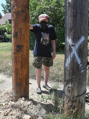 Larry Kope stands Wednesday between a recently-installed power pole (left) and the old one in the tree lawn of his Coventry Boulevard NE home in Canton. Kope said the new pole damaged his sewer drain.
