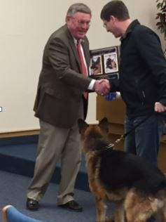 The Oshkosh Police Department announced the retirement of canine Sony at the Common Council meeting April 11. Mayor Steve Cummings congratulates Sony and Officer Brian Denor.