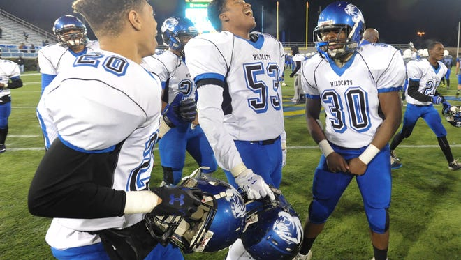 Howard's Kevin Womack (20), Christian Francis (53) and Hissan Snell (30) celebrate the Wildcats; 28-13 win over St. Georges on Dec. 5 for Howard's first DIAA Division II football championship.
