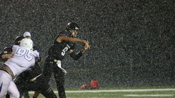 Under a heavy rain, Franklin quarterback Max Alba lets fly a pass as Oak Creek lineman Collin Ciombor is blocked during the Sabers' 33-21 win on Sept. 16. Alba threw for 275 yards and four TDs in the contest.