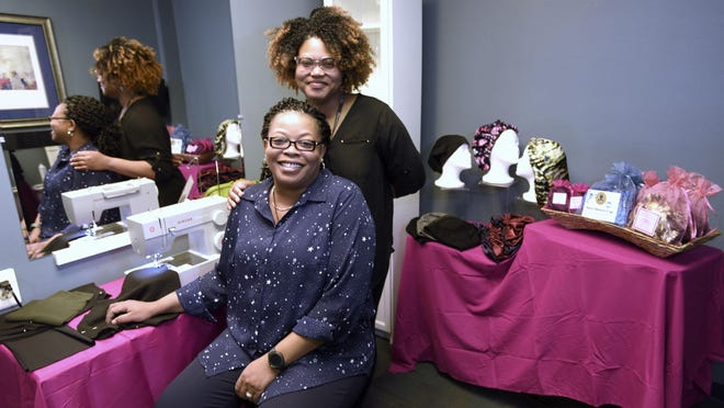 Embrace the Natural You owner Genevieve Anyiah stands behind sister Pearl Renee Goss.