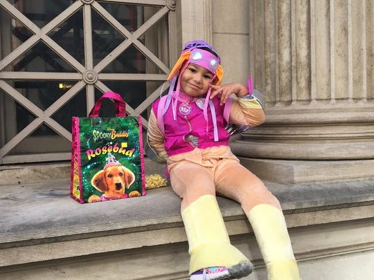 """AnnaSophia Johnakin, of Staunton, poses for a photo dressed as """"Skye"""" from the TV series PAW Patrol, during the Halloween downtown trick-or-treating event in Staunton, Va., on Saturday, Oct. 28, 2017."""
