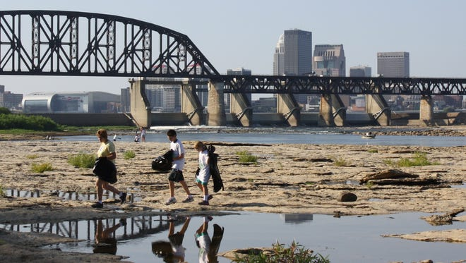 Visitors walk along the banks of the Ohio at the Falls of the Ohio State Park.
