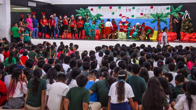 Santa Claus, portrayed by Deacon Len Stohr, Island Success Through Learning Association Inc. president, and Mrs. Claus, portrayed by Navy Rear Adm. Shoshana Chatfield, Joint Region Marianas commander, are joined onstage by helper elves and others at Upi Elementary School in Yigo on Thursday, Dec. 21, 2017.