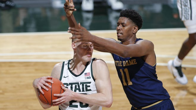 Michigan State's Joey Hauser, left, and Notre Dame's Juwan Durham vie for a rebound during the first half of an NCAA college basketball game, Saturday, Nov. 28, 2020, in East Lansing, Mich.