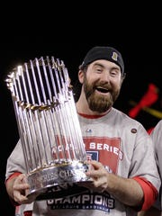 Jason Motte of the Cardinals celebrates with the World Series trophy in 2011.