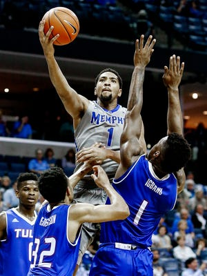 University of Memphis forward Dedric Lawson (top) drives to the basket against University of Tulsa defenders Corey Henderson Jr. (left) and Martins Igbanu (right) during second half action of a Tigers 66-44 victory at the FedExForum.