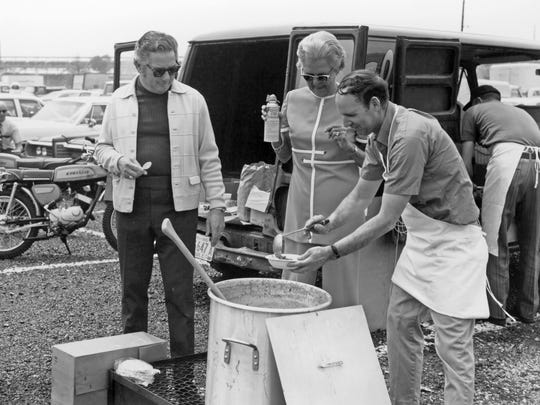Mary Unser (second from right) watches as a bowl of her chili is ladled for two-time Indy 500 winner Rodger Ward (to her right).