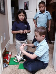 Natalia Eberhard, 9, and her brothers David, 7, and Wade, 7, seated, play with Legos together in their home in Keene Township. Angie and Tim Eberhard have three biological children, and they adopted Natalia and David from Ecuador.