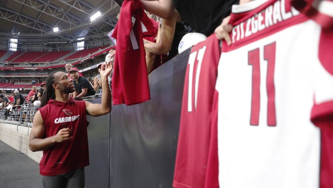Arizona Cardinals wide receiver Larry Fitzgerald (11) signs autographs for fans during camp at University of Phoenix Stadium in Glendale, Ariz. August 8, 2018.