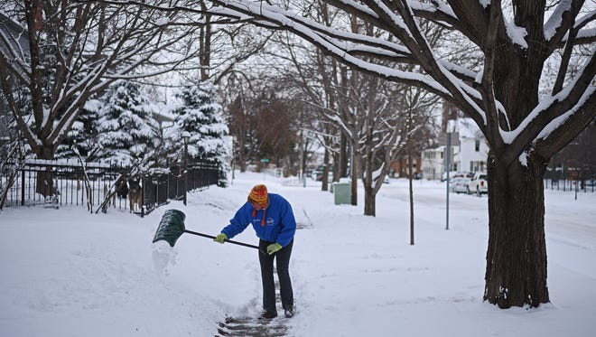 Jackie Ritter shovels the sidewalk outside her house Friday, Feb. 24, 2017, in Sioux Falls after a snow storm Thursday and Friday morning.