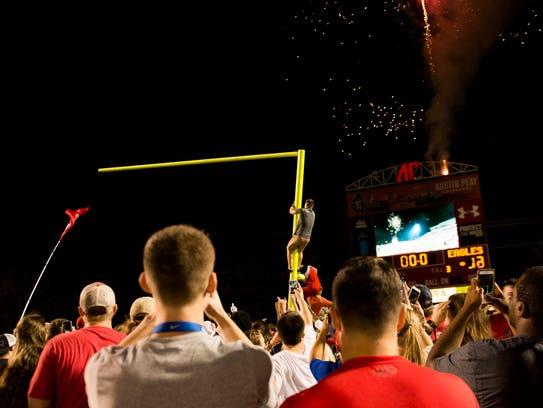 Students help tear down a goal post as fireworks go