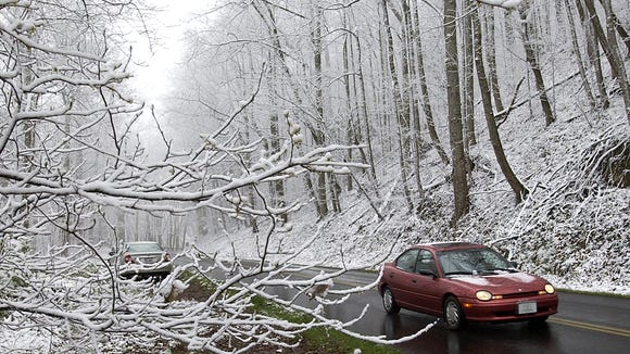 Cars drive along a snow-dusted Blue Ridge Parkway in this file photo.