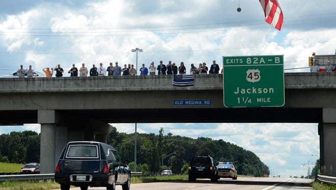 Members of Jackson Police Department, Madison County Sheriff's Office, Tennessee Highway Patrol, Jackson Fire Department and Tennessee Bureau of Investigation stand on the Old Medina Road overpass on Interstate 40 in Jackson in salute as the hearse carrying the body of fallen TBI Special Agent De'Greaun Frazier proceeds through Jackson, Wednesday afternoon.
