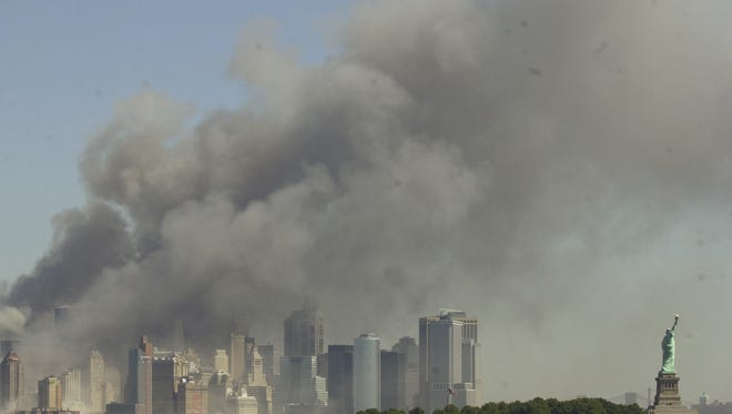 The Statue of Liberty, right, stands at the entrance to New York Harbor as the Twin Towers of the World Trade Center burn in this view from Jersey City, N.J. on Sept. 11, 2001.