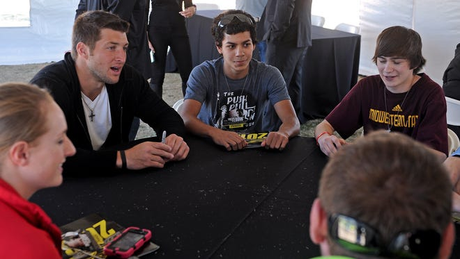 """Tim Tebow, second from left, talks with fans during a meet-and-greet before the Wichita Falls Nighthawks season opener in 2013. Tebow was home-schooled but played sports on his local public school team. A bill filed by two lawmakers, Rep. James Frank (R-Wichita Falls) and Sen. Van Taylor (R-Plano), seeks to provide """"equal opportunity"""" for home-schooled students to participate in UIL activities. The bill is called the """"Tebow Bill,"""" after Tim Tebow."""