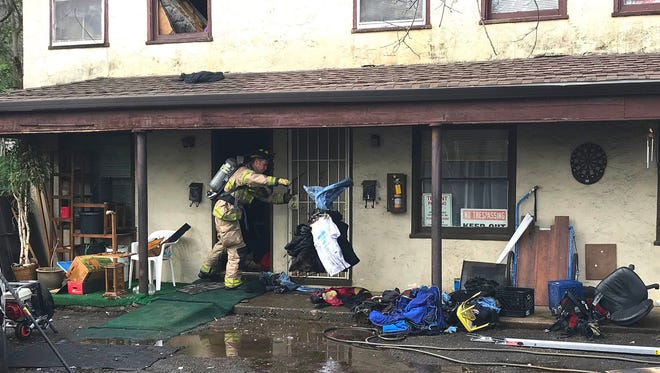 Firefighters clean out an apartment where a fire started Sunday, Jan. 7, 208, when a resident tried to kill a spider using a torch lighter.
