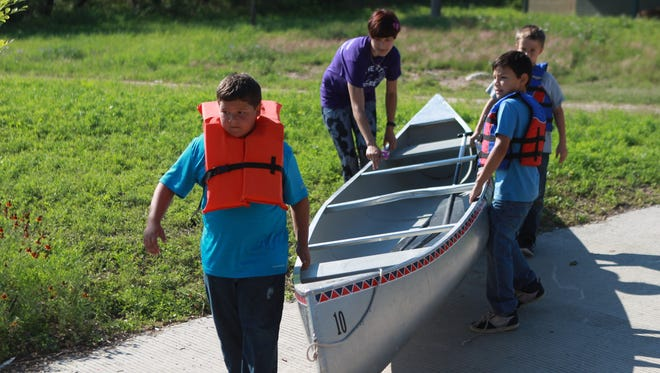 Campers help their camp mentor lower a canoe into the Concho River during a summer camp.