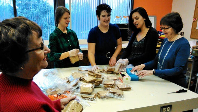 """Judy Terry and First Presbyterian Church staff members, from left, Erin Landsee, Leah Bergman, Anna Sheetz and Judy Whitford prepare a pile of """"Sunday Sandwiches"""" for Iowa City people who could use one."""