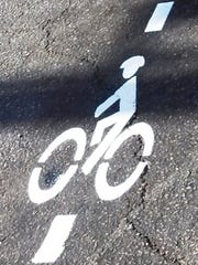 A bicycle detector pavement marking has vertical lines at the top and bottom but no arrows.