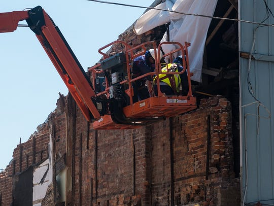 Two construction workers tear down brick connected
