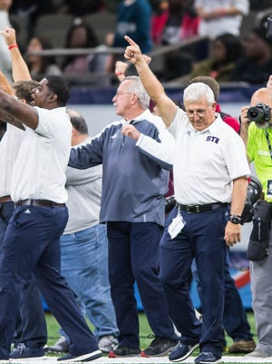 Head coach Jim Hightower raises his hand in victory as his St. Thomas More Cougars won the first state championship in school history on Friday in the Superdome.