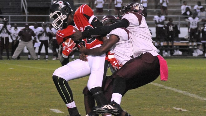 Parkway tight end Artavious Lynn drags two Booker T. Washington defenders in first period action Friday.