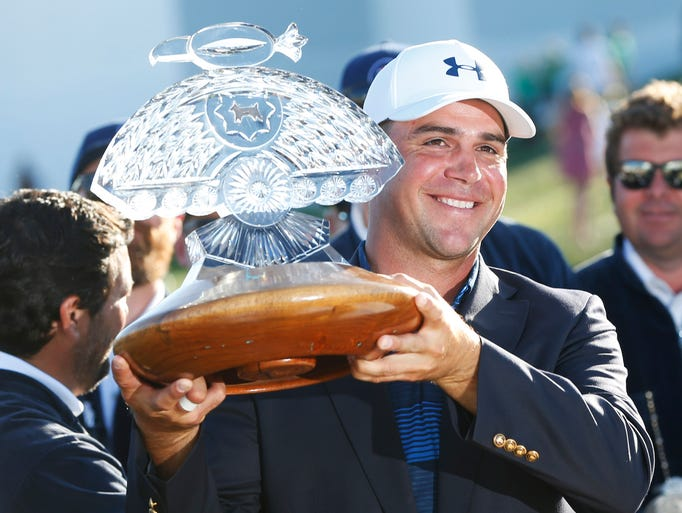 Gary Woodland holds the trophy after winning the Waste